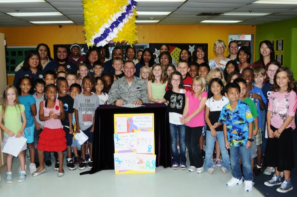 """ANDERSEN AIR FORCE BASE, Guam – Brig. Gen. John Doucette, 36th Wing commander, poses for a photo with faculty and children from the Child Development Center before signing the Child Abuse Prevention Month Proclamation April 6. """"Healthy Kids, Strong Families"""" is a topic that is being taught to the children and parents of Team Andersen, encouraging families to talk with each other and children to be active in sharing things with their parents. (U.S. Air Force photo/ Senior Airman Carlin Leslie)"""