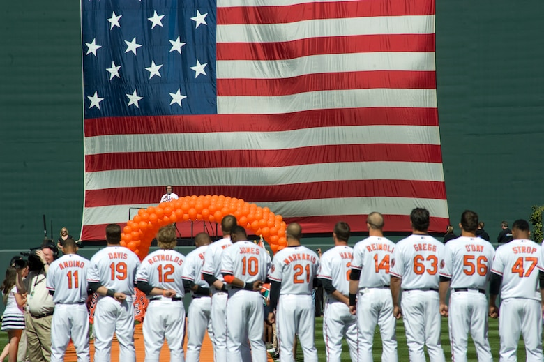 BALTIMORE, Md. -- Members of the Baltimore Orioles observe the singing of The National Anthem before their season opener April 4.  The 1st Helicopter Squadron from Joint Base Andrews, Md., contributed to the ceremonies with a flyover display during closing notes of The National Anthem.    (Photo/Bobby Jones)