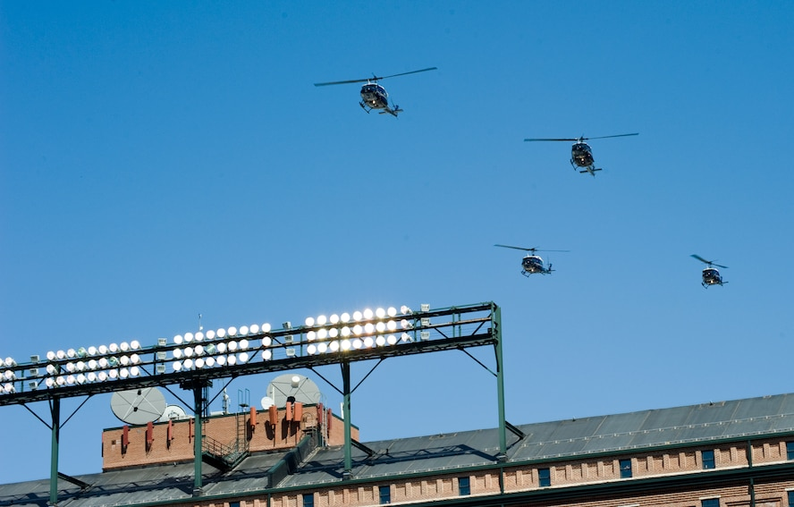 BALTIMORE, Md. -- A formation of 1st Helicopter Squadron UH-1N Iroquois from Joint Base Andrews, Md., fly in formation over the Camden Yards Stadium during the last note of The National Anthem at the Baltimore Orioles' season opener April 4.  These patriotic displays of military strength and precision require a considerable amount of advanced planning and coordination, but are an important part of showing the American people that their Air Force is the best in the world.   (Photo/Bobby Jones)