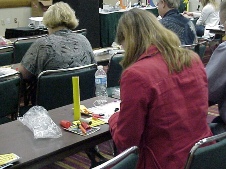 """Teachers from across the nation build rockets during Cindy Henry's presentation """"Launch into STEM with Model Rocketry"""" during the National Science Teachers Association Conference in Indianapolis. (U.S. Air Force photo)"""