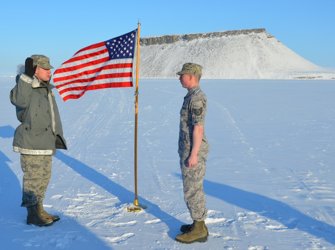 THULE AIR BASE, Greenland – 1st Lt. Ariel Torgerson (left), 821st Support Squadron Communications Flight commander, issues the oath of enlistment to Staff Sgt. Eric Jennings, 821st SPTS, March 30 in view of Mount Dundas, Greenland. The 821st Air Base Group, which operates the base, is one of the 21st Space Wing's groups and is home to the northernmost deep water port in the world. Jennings took advantage of the unique opportunity to have his re-enlistment take place on the ice of the North Bay. He is a client systems technician and re-enlisted for five more years of service. (U.S. Air Force photo/Tech. Sgt. Darrell Kinsey)