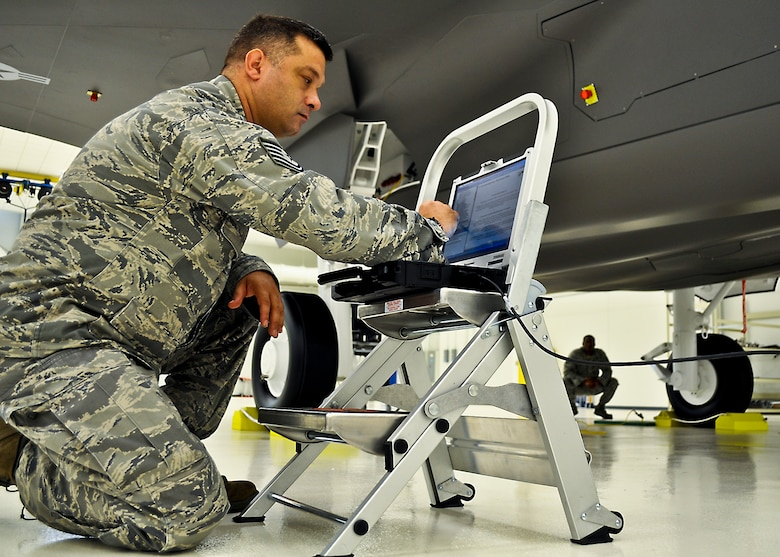 Tech. Sgt. Brandon Sullivan, an aircraft armament systems technician with the 33rd Aircraft Maintenance Squadron, is using a portable maintenance device loaded with joint technical data and plugged into an F-35 life-sized trainer during a weapons familiarization course. Training indoors allows for deliberate training for the maintainers without having to take a real jet off the flight line thus competing with pilot training. Later training on the flight line is streamlined due to the preparation on the mock-ups. The 17-day weapons familiarization class was the first-ever weapons course completed since Eglin's F-35 Academic Training Center began commencement of formal training Mar 19. (U.S. Air Force photo/Maj. Karen Roganov)