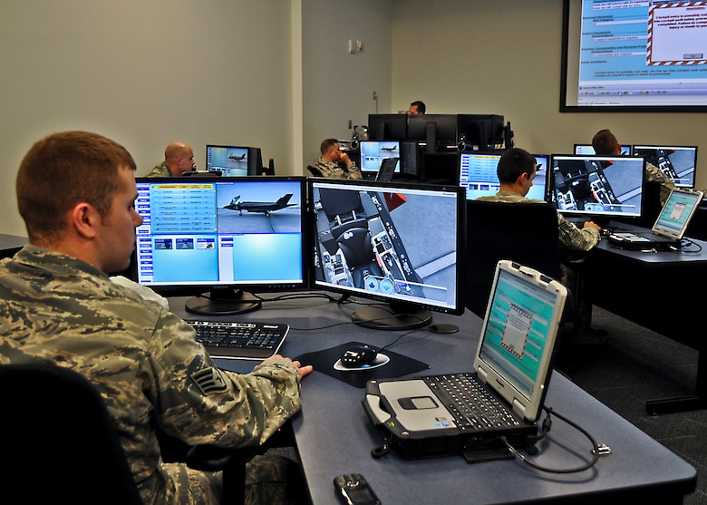 Staff Sgt. Guin Duprey I, of the 31st Test and Evaluation Squadron, Edwards Air Force Base, Fla., familiarizes himself with the F-35 Joint Strike Fighter using the desktop virtual-reality aircraft systems maintenance trainer, as well as a laptop loaded with joint technical data that is used for flight line operations. The 17-day weapons familiarization class was the first-ever weapons course completed since Eglin's F-35 Academic Training Center began commencement of formal training Mar 19. The ATC is a first-of-its-kind facility for F-35 pilot and maintenance training and uses a cascading style of learning using computers and hands-on equipment to build upon skills.  (U.S. Air Force photo/Maj. Karen Roganov)