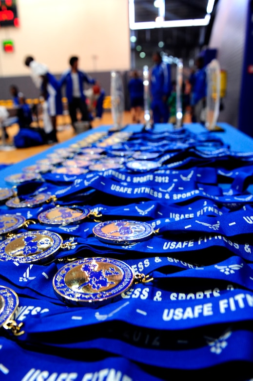 Medals and trophies sit on the sideline waiting to be handed out to the victors of the U.S. forces in Europe basketball tournament, Ramstein Air Base, Germany, April 8, 2012. (U.S. Air Force photo/ Senior Airman Aaron-Forrest Wainwright)