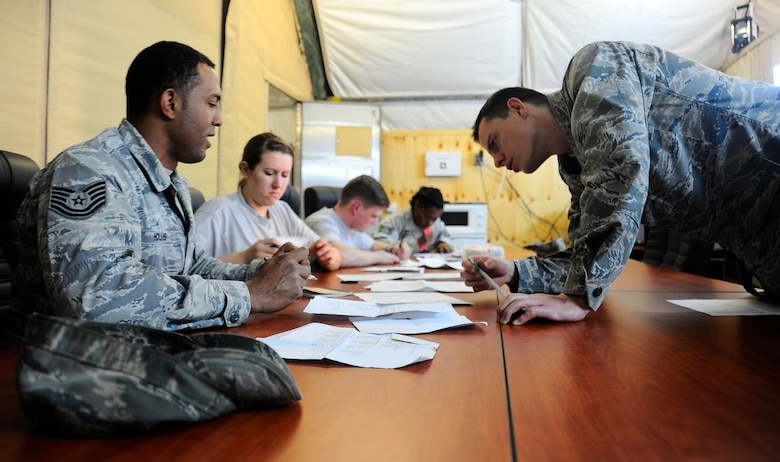 Second Lt. Justin Miller checks Tech. Sgt. Nicholas Hollis' assignment April 3, 2012, during a basic Russian language class at the Transit Center at Manas, Kyrgyzstan. The class is hosted by the Theater Security Cooperation division twice a week for two months. Miller is the 376th Air Expeditionary Wing TSC host nation liaison branch chief and is deployed here from Beale Air Force Base, Calif. Hollis is a 376th Expeditionary Logistics Readiness Squadron petroleum, oil and lubricants distribution supervisor deployed here from Spangdahlem Air Base, Germany. (U.S. Air Force photo/Staff Sgt. Angela Ruiz)