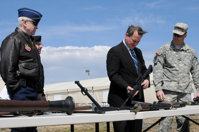 Massachusetts Lt. Gov. Timothy Murray and acting Adjutant General of the Massachusetts National Guard Maj. Gen. L. Scott Rice observe various weapons on display with Sgt. John Slager, Camp Edwards training manager, during a tour of the Massachusetts Military Reservation, April 9.  Murray is currently touring military installations across Massachusetts with members of the state's Military Asset and Security Strategy Task Force in support of protecting the missions, jobs and economic investments associated with the bases. (Air National Guard photo by Tech. Sgt. Kerri Cole/Released)