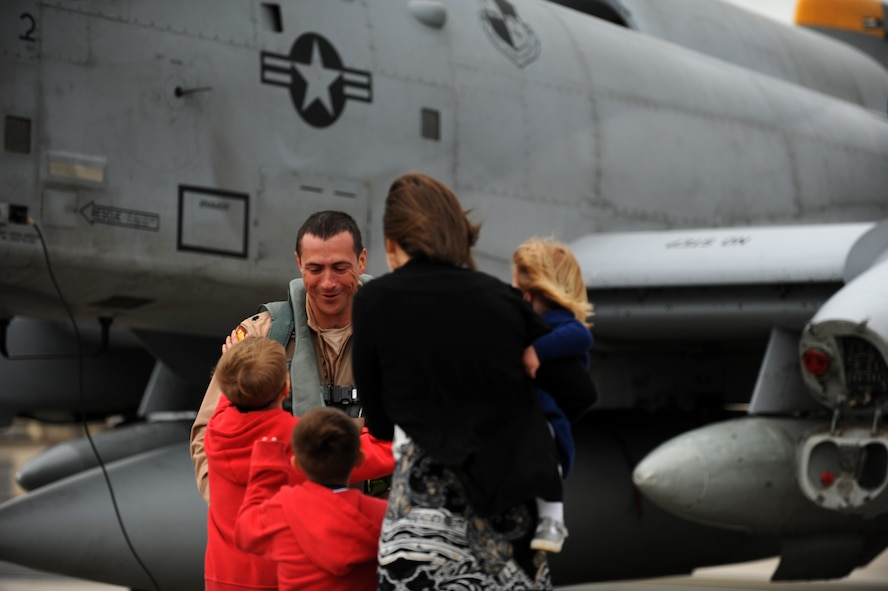 SPANGDAHLEM AIR BASE, Germany – Lt. Col. Joshua Ruddell, 81st Fighter Squadron pilot and director of operations, is welcomed home by his wife, Neva, and children, from left, Tyler, Carter and Bella on Ramp 4 here April 10 after returning from his deployment from Bagram Airfield, Afghanistan. Ruddell was one of the squadron's six pilots who had been providing close air support during Operation Enduring Freedom. (U.S. Air Force photo by Airman 1st Class Matthew B. Fredericks/Released)