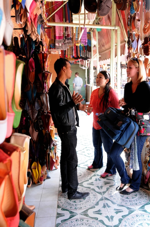 MOROCCO, Marakech -- Capt. Sylvia Kim, left, U.S. Air Forces Africa interpreter, interprets the French-speaking language for U.S. Army Sgt. Abigail Waldrop, AFAFRICA American Forces Network, as a French speaking vendor tells Waldrop and Kim about the shoes he is selling at the Jemaa el Fna Market here April 2. Kim and Waldrop visited the market with a group of service members as part of a culture exploration day before supporting the Marrakech Aeroexpo 2012. U.S. Air Forces Africa is participated in the third biennial Aeroexpo Marrekech to strengthen the partnerships with the nations involved and show commitment to security and stability in the region. This group of service members looked out for one another on their trip to the market ensuring no one was lost, left behind or injured. (U.S. Air Force photo by Senior Airman Natasha Stannard/Released)