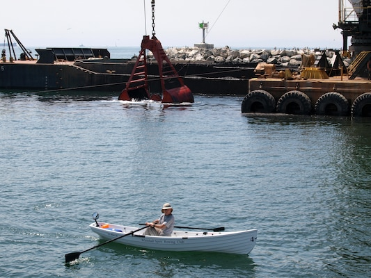 A Whitehall Spirit Rowing Club member rows past the dredge Paula Lee April 8 at Marina del Rey Harbor. The dredge is removing sediment from the navigation channel to enhance safety for government, commercial and recreational boaters.