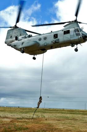 A Marine from the 15th Marine Expeditionary Unit's Maritime Raid Force fast-ropes from a CH-46E Sea Knight during a fast-roping exercise, here, April 11. The MRF's primary role is to carry out raids against maritime objectives including gas and oil platforms, ships and targets on shore. This was the first time the MRF was able to practice their unique skill sets as a cohesive unit.