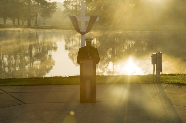 Navy Lt. Kenneth Miller, base chaplain, Marine Corps Logistics Base Albany, delivers an Easter sunrise message as the sun rises over Covella Pond Sunday morning.