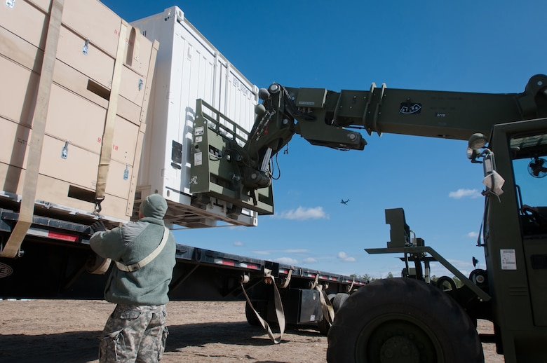 Army Sgt. Japheth Forehand, distribution NCO for the U.S. Army's 690th Rapid Port Opening Element in Fort Eustis, Va., secures a cargo container to a flatbed trailer as another is maneuvered into place and a C-17 flies overhead March 29, 2012, at Joint Base McGuire-Dix-Lakehurst, N.J. Forehand was working at the Forward Node of a Joint Task Force-Port Opening during Eagle Flag, a U.S. Air Force-sponsored exercise to prepare units for operating in deployed environments. The Kentucky Air National Guard's 123rd Contingency Response Group operated the airlift side of the JTF-PO, known as an Aerial Port of Debarkation. (U.S. Air Force photo by Maj. Dale Greer)