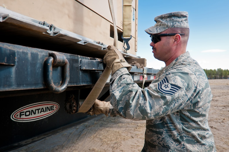 Tech. Sgt. Jeremy Hitt, a vehicle operator from the 22nd Logistics Readiness Squadron at McConnell Air Force Base, Kan., straps cargo to a flatbed trailer March 29, 2012, at Joint Base McGuire-Dix-Lakehurst, N.J. Hitt was working at the Forward Node of a Joint Task Force-Port Opening during Eagle Flag, a U.S. Air Force-sponsored exercise to prepare units for operating in deployed environments. The Kentucky Air National Guard's 123rd Contingency Response Group operated the airlift side of the JTF-PO, known as an Aerial Port of Debarkation. (U.S. Air Force photo by Maj. Dale Greer)