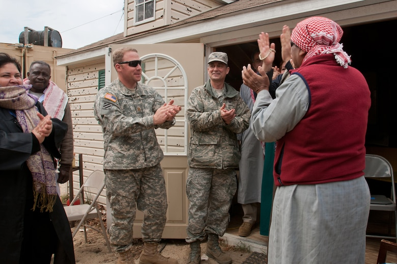 Role-playing actors give Col. Warren Hurst (center), commander of the Kentucky Air National Guard's 123rd Contingency Response Group, and Army Maj. Keith Pruett, commander of the 690th Rapid Port Opening Element from Fort Eustis, Va., an Arabic welcome to the fictional village of Sabor, Nessor, on March 28, 2012. Both were participating in Eagle Flag, an exercise designed to simulate a deployed environment at Joint Base McGuire-Dix-Lakehurst, N.J. (U.S. Air Force photo by Maj. Dale Greer)