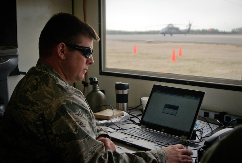Maj. Ash Groves, air operations officer for the Kentucky Air National Guard's 123rd Contingency Response Group, monitors air traffic March 28, 2012, at Lakehurst Naval Air Engineering Station, N.J., while sitting in a Hard-sided Expandable Lightweight Air-Mobile Shelter. The HELAMS served as a Joint Operations Center for Army and Air Force personnel running a Joint Task Force-Port Opening as part of Eagle Flag, an exercise designed to test the ability of U.S. forces to operate in a deployed environment. (U.S. Air Force photo by Master Sgt. Phil Speck)