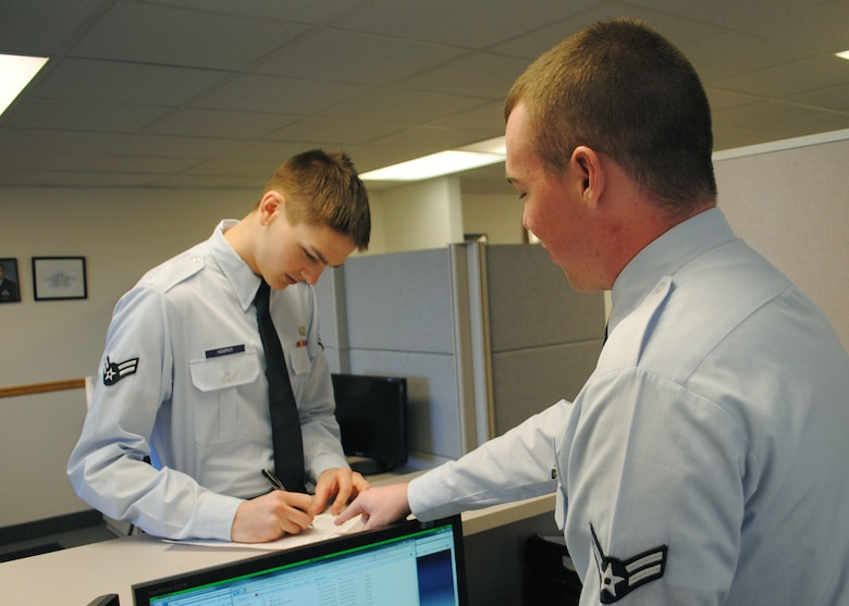 Airman 1st Class Richie Peart, right, 341st Comptroller Squadron customer service technician, helps Airman 1st Class Nathaneal Hooper, 341st Force Supports Squadron customer service, fill out an Air Force form. (U.S. Air Force photo/Airman 1st Class Cortney Paxton)