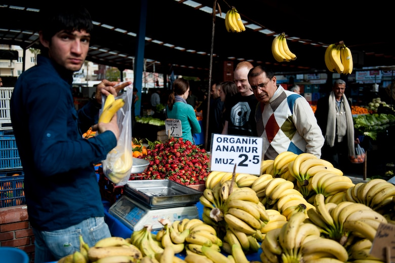 Mehmet Birbiri and Senior Airman Clayton Lenhardt, 39th Air Base Wing Public Affairs, stop at a fruit stand during a trip to a farmers market March 8, 2012, in Adana, Turkey. The fertile soil around Adana allows farmers to grow many types of produce, keeping prices low and fruits and vegetables fresh. (U.S. Air Force photo by Tech. Sgt. Michael B. Keller/Released)