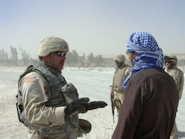 AFGHANISTAN — Dan Potter (left), contracting officer's representative, 533rd Engineer Detachment, clarifies requirements for grading a temporary access road to Kandahar Airfield with the Afghan contractor on May 21, 2011.