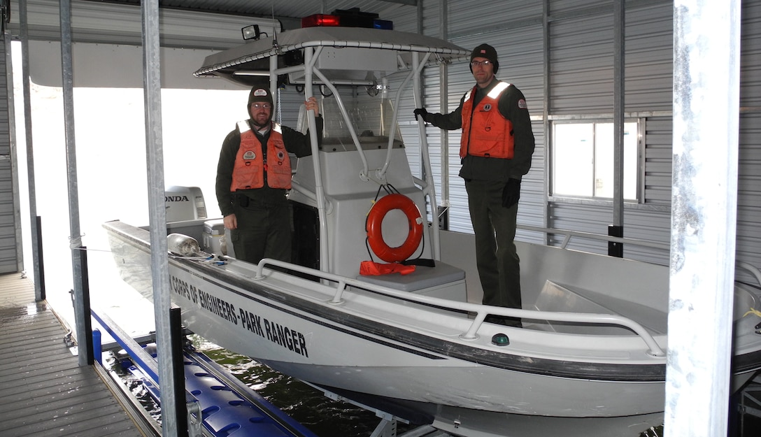 COCHITI LAKE, N.M. - Park Rangers Chris Schooley (left) and Nicholas Parks situate the Cochiti Lake Project's boat in the dock.