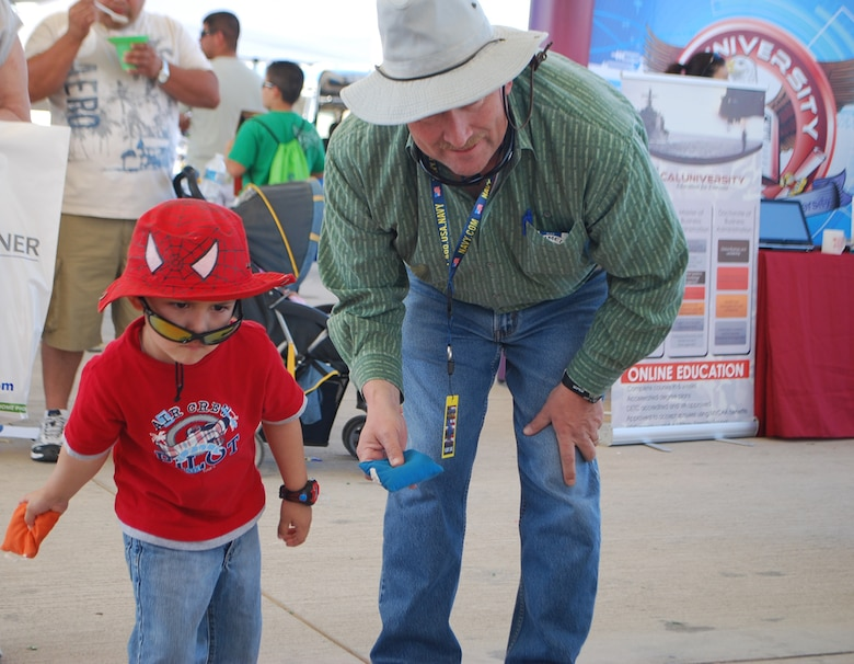 EL CENTRO, Calif. - A young visitor to the air show learned about UXO by talking to FUDS Project Manager Sonny Franks (right).  He also spent time playing a beanbag toss game at the FUDS booth.