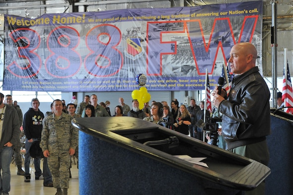 Col. Scott Long, 388th Fighter Wing commander, greets the large group of returnees April 7 with a banner to his right welcoming home the Airmen. (U.S. Air Force photo by Alex Lloyd)