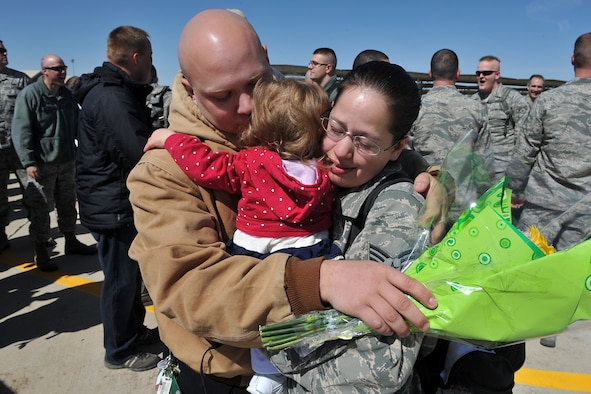 A husband greets his wife, Sr. Airman Theresa Speer of the 388th Fighter Wing Component Maintenance Squadron, with their baby in arms April 7 as nearly 200 Airmen from the 421st Fighter Squadron return to Hill Air Force Base. (U.S. Air Force photo by Alex Lloyd)