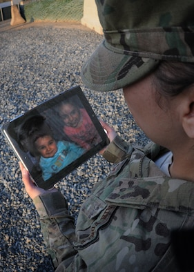 Staff Sgt. Nadine Barclay, a photojournalist deployed from Aviano Air Base, Italy, to the 438th Air Expeditionary Wing in Kabul, Afghanistan, holds a photo of her daughters, Avah and Sophia, as she reflects on the importance of honoring those that serve without the uniform, April 2, 2012. The San Antonio, Texas native is currently deployed on a six-month deployment as an advisor to Afghan air force public affairs airmen at Kabul International Airport. (U.S. Air Force photo by Tech. Sgt. Jeremy Larlee)