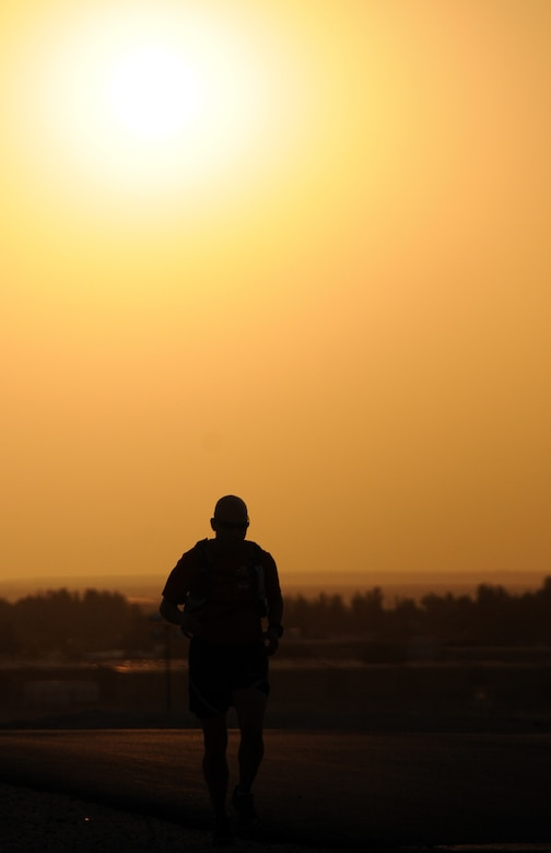 U.S. Air Force Tech. Sgt. Wayne Jenderny, 386th Expeditionary Civil Engineering Squadron firefighter, runs as the sun sets at an undisclosed location, Southwest Asia, April 7, 2012. Jenderny, a Minnesota Air National Guard member deployed from the 148th Fighter Wing and native of Eyota, Minn., ran 100 miles in less than 24 hours to raise awareness and take donations for a fellow firefighter's daughter who is suffering from a painful nerve disorder. (U.S. Air Force photo by Staff Sgt. James Lieth)
