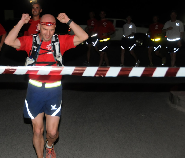 U.S. Air Force Tech. Sgt. Wayne Jenderny, 386th Expeditionary Civil Engineering Squadron firefighter, crosses the finish line after completing 100 miles in less than 24 hours at an undisclosed location, Southwest Asia, April 7, 2012. Jenderny, a Minnesota Air National Guard member deployed from the 148th Fighter Wing and native of Eyota, Minn., ran 100 miles in less than 24 hours to raise awareness and take donations for a fellow firefighter's daughter who is suffering from a painful nerve disorder. (U.S. Air Force photo by Staff Sgt. James Lieth)