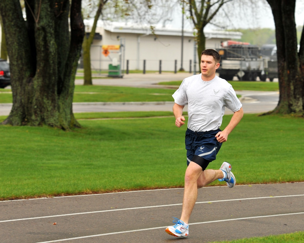 """Airman 1st Class Robert Miles, 115th Force Support Squadron, runs on the Truax Field track as part of his annual physical fitness assessment April 15. Miles finished with a time of 7:59 which put him in the """"Excellent"""" category with a perfect overall scoree of 100. Miles is also training for the National Guard Marathon in Lincoln, Neb., for a chance to make the National Guard Marathon Team which travels around the country to compete. Wisconsin Air National Guard photo by Tech. Sgt. Jon LaDue"""