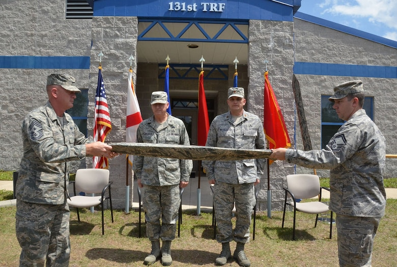 Florida Air National Guard State Command Chief Master Sgt. Robert Lee (left) and Senior Master Sgt. Cory Brown (right) unveil the new official colors for the 131st Training Flight at Camp Blanding Joint Training Center, April 12, 2012. Commander of the Florida Air National Guard Brig. Gen. Joseph Balskus (second from left) and 131st Commander Maj. John Waltbillig also participated in the afternoon ceremony, during which the Florida Air National Guard's Weather Readiness Training Center (WRTC) was deactivated, and replaced, as the 131st Training Flight was activated. Photo by Debra Cox
