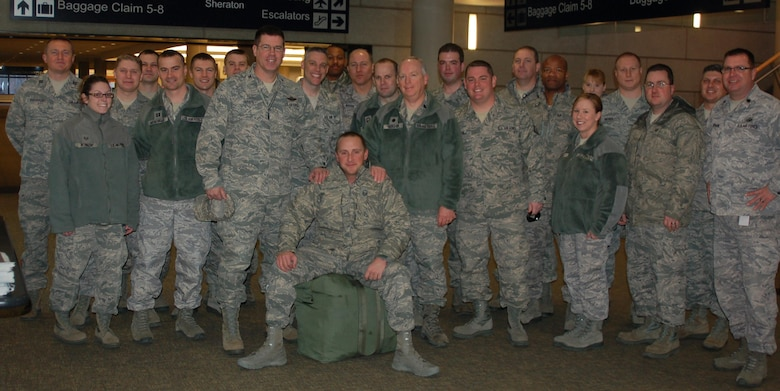 Master Sgt. Robert E. Bailey rests on his luggage and is surrounded by fellow members of the 103rd Air Operations Group who welcomed him home at Bradley International Airport Feb. 10, 2012, following an seven-month deployment to the Combined Air and Space Operations Center in Southwest Asia where he served as the Superintendent of the Targeting and Imagery Support Element. While deployed, Bailey was recognized for his excellence and selected to be the SNCO of the Year for the state of Connecticut. (U.S. Air Force photo by Capt. Jefferson S. Heiland)