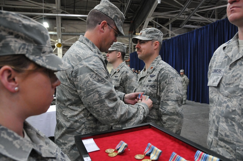 Col. Peter DePatie, 103rd Air Operations Group commander, pins medals on Maj. Greg Kozbinski during a Joint Freedom Salute Ceremony in the main hangar at Bradley Air National Guard Base in East Granby, Conn. March 31, 2012. Airmen and Soldiers of the Connecticut National Guard were formally welcomed home and honored following deployments over the past year. (U.S. Air Force photo by Tech. Sgt. Erin McNamara\RELEASED)