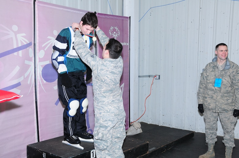 Senior Airman Christopher Keogan of the 103rd Air Operations Group awards a medalist at the Special Olympics March 4, 2012, held at the international skating center in Simsbury, Conn. Several members of the Connecticut Air National Guard volunteered to help staff the event. (U.S. Air Force photo by Airmen 1st Class Emmanuel Santiago/Released)