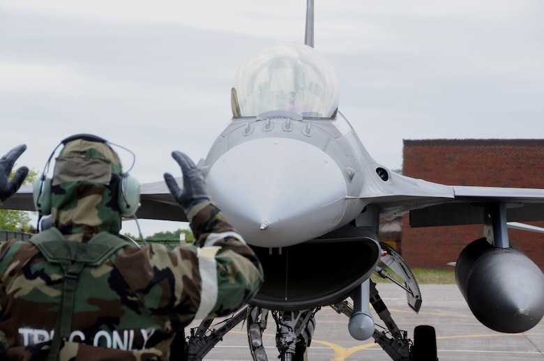 A crew chief from the 148th Fighter Wing, Duluth, Minn. guides an F-16 Fighting Falcon pilot to a stop during an operational readiness exercise.  The exercise was designed to refamiliarize Airmen with Force Protection Conditions, Mission Oriented Protection Postures and for members to perform the mission while wearing the Chemical Protective Overgarment. (U.S. Air Force photo by Senior Airman Sarah Hayes.)