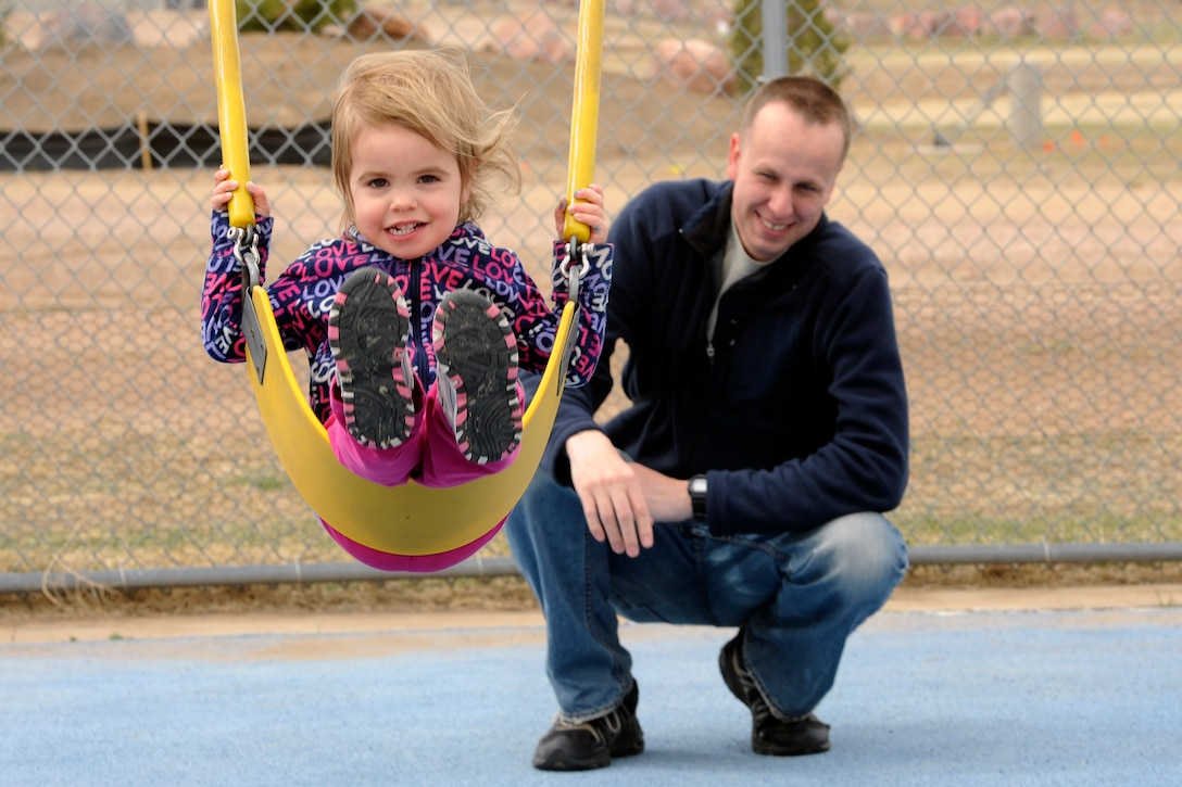 Heidi Dietrich and her father, Staff Sgt. Kenneth Dietrich, enjoy the swings during the Month of Military Child Carnival April 13 at the Child Development Center. Some of the fun activities included face painting, tug of war and fishing. (U.S. Air Force photo/Bill Evans)