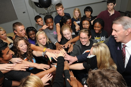The Randolph High School Student Council puts their hands in to do a final cheer April 13 after being awarded a $20,000 check by San Antonio Spurs representatives. The student council was selected for their DriveSMART campaign by the Silver and Black Give Back's Team Up Challenge. (U.S. Air Force photo by Melissa Peterson)