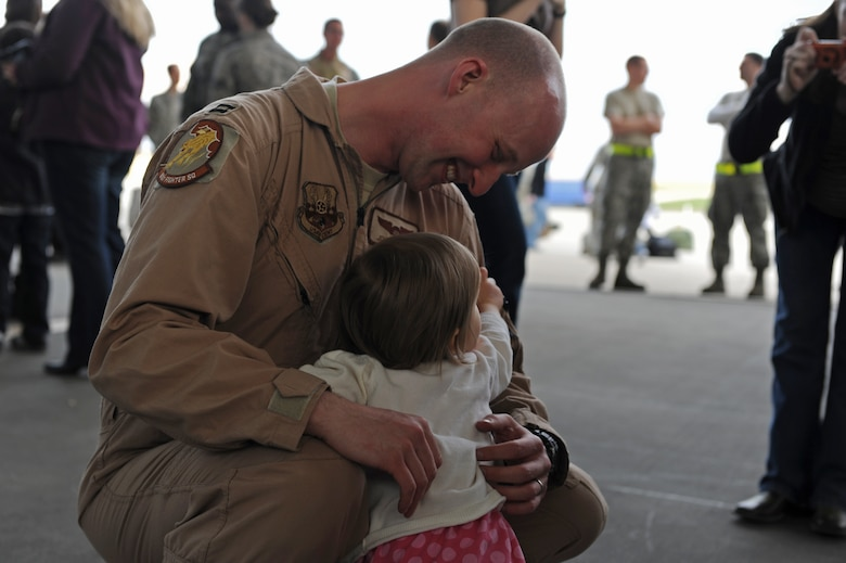 SPANGDAHLEM AIR BASE, Germany – Capt. John Cotman, 81st Fighter Squadron A-Flight commander, embraces his daughter on Ramp 3 here April 13. Family and friends waited at Hangar 3 to welcome home more than 70 Airmen from a deployment with 81st Fighter Squadron to Bagram Airfield, Afghanistan, who had been providing close-air support during Operation Enduring Freedom. (U.S. Air Force photo by Airman 1st Class Matthew B. Fredericks/Released)