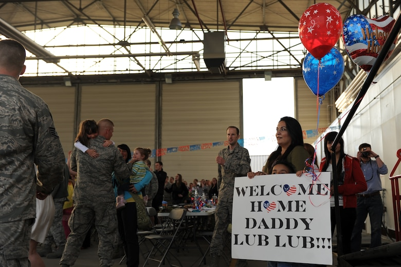 SPANGDAHLEM AIR BASE, Germany – Rene Bernal holds up a sign while waiting with his mother, Patricia, to welcome home his father, Staff Sgt. Christopher Bernal, 81st Aircraft Maintenance Unit weapons load crew team chief, on Ramp 3 here April 13. Family and friends waited at Hangar 3 to welcome home more than 70 Airmen from a deployment with 81st Fighter Squadron to Bagram Airfield, Afghanistan, who had been providing close-air support during Operation Enduring Freedom. (U.S. Air Force photo by Airman 1st Class Matthew B. Fredericks/Released)