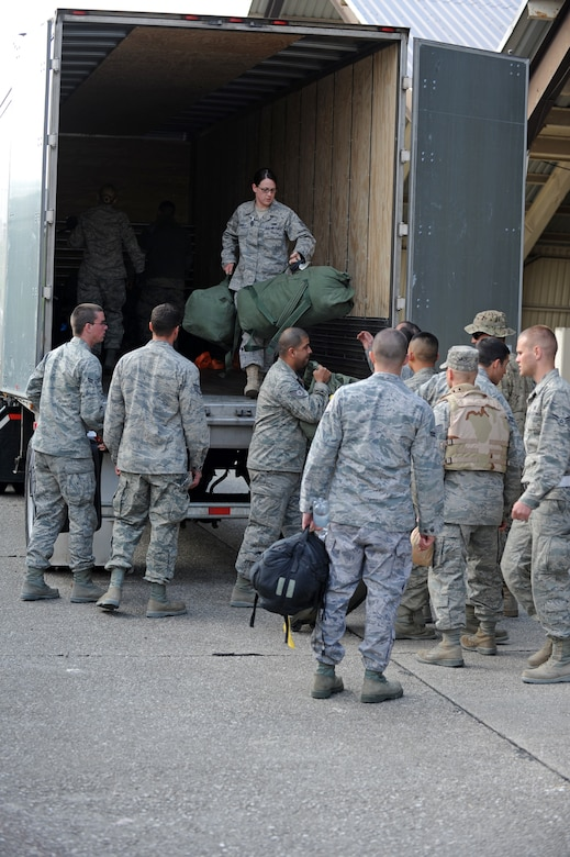 SPANGDAHLEM AIR BASE, Germany – Airmen from the 52nd Fighter Wing unload baggage in preparation for a customs inspection on Ramp 3 here April 13. Family and friends waited at Hangar 3 to welcome home more than 70 Airmen from a deployment with 81st Fighter Squadron to Bagram Airfield, Afghanistan, who had been providing close-air support during Operation Enduring Freedom. (U.S. Air Force photo by Airman 1st Class Matthew B. Fredericks/Released)
