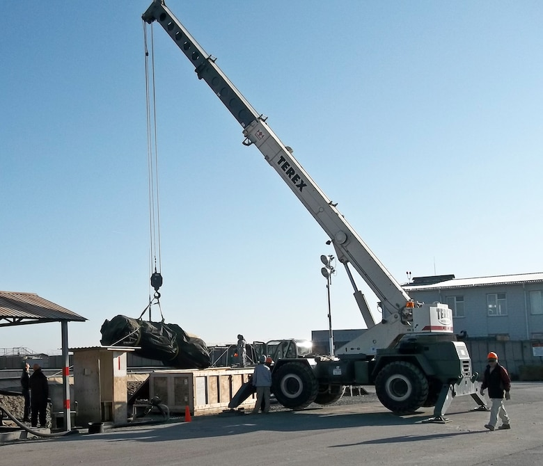 Members of the 376th Expeditionary Civil Engineer Squadron horizontal shop operate a crane to hoist a fuel bladder into place March 27, 2012, during a fuel tank and berm liner change at the Transit Center at Manas, Kyrgyzstan. The 1,200-pound berm liner and 7,500-pound fuel tank took four days to change; the 376th ECES removed the old ones from the containment area.  (U.S. Air Force courtesy photo)
