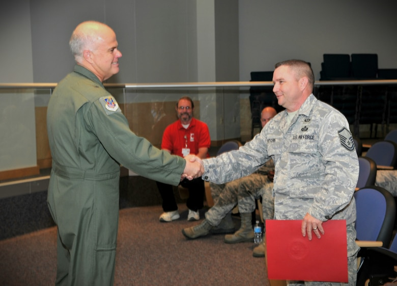Brig. Gen. Tony McMillan, commander, 145th Airlift Wing, congratulates Master Sgt. Robert C. Ritchie of the 118th Air Support Operations Squadron, North Carolina Air National Guard for being awarded the American Red Cross Certificate of Recognition for Extraordinary Personal Action by Tim Patton of the Carolina Piedmont Region of the American Red Cross. In early March Ritchie provided medical attention to a woman pinned between a vehicle and a wall. The Certificate of Recognition for Extraordinary Personal Action is one of the highest awards given by the American Red Cross.