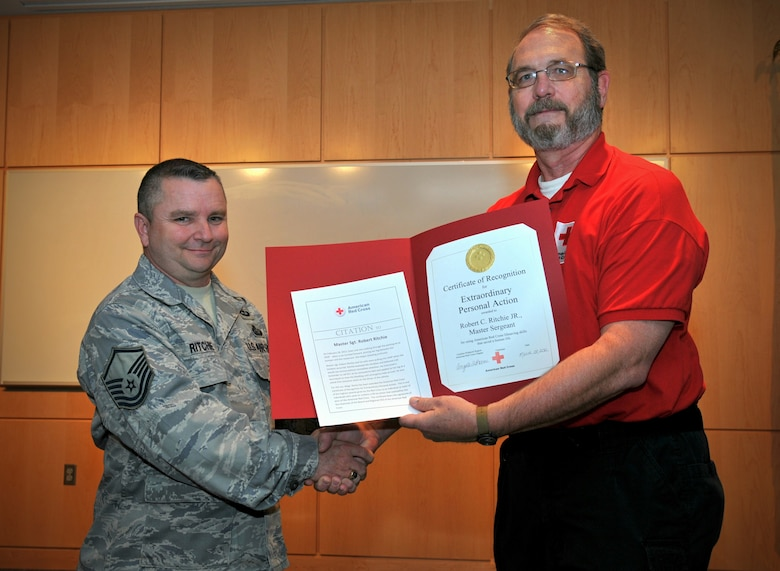 Master Sgt. Robert C. Ritchie of the 118th Air Support Operations Squadron, North Carolina Air National Guard is awarded the American Red Cross Certificate of Recognition for Extraordinary Personal Action by Tim Patton of the Carolina Piedmont Region of the American Red Cross. In early March Ritchie provided medical attention to a woman pinned between a vehicle and a wall. The Certificate of Recognition for Extraordinary Personal Action is one of the highest awards given by the American Red Cross.