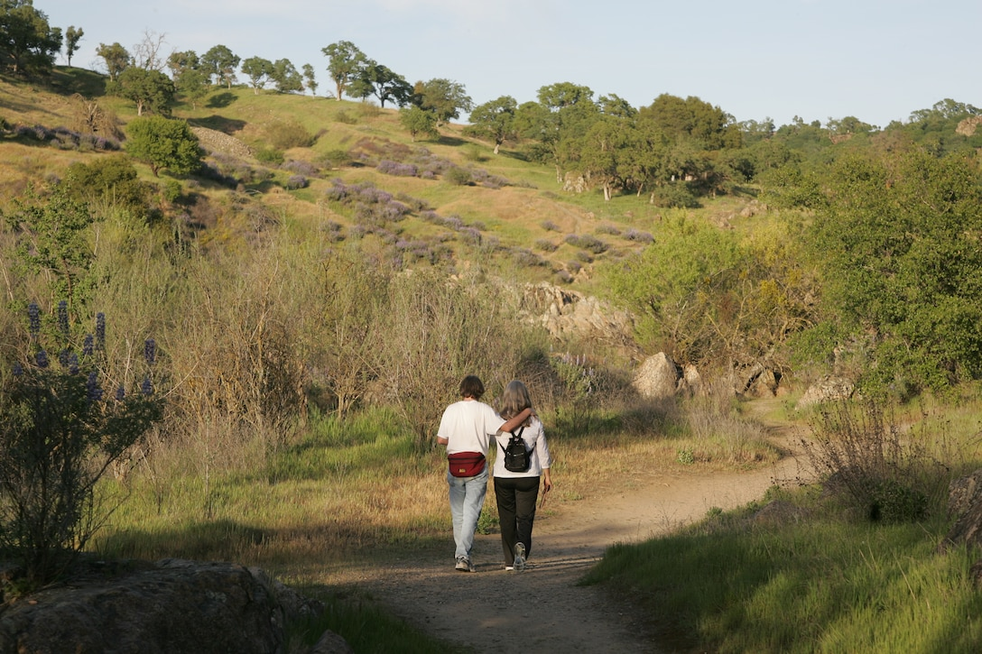 A couple enjoys a quiet stroll beside the river at Stanislaus River Parks.