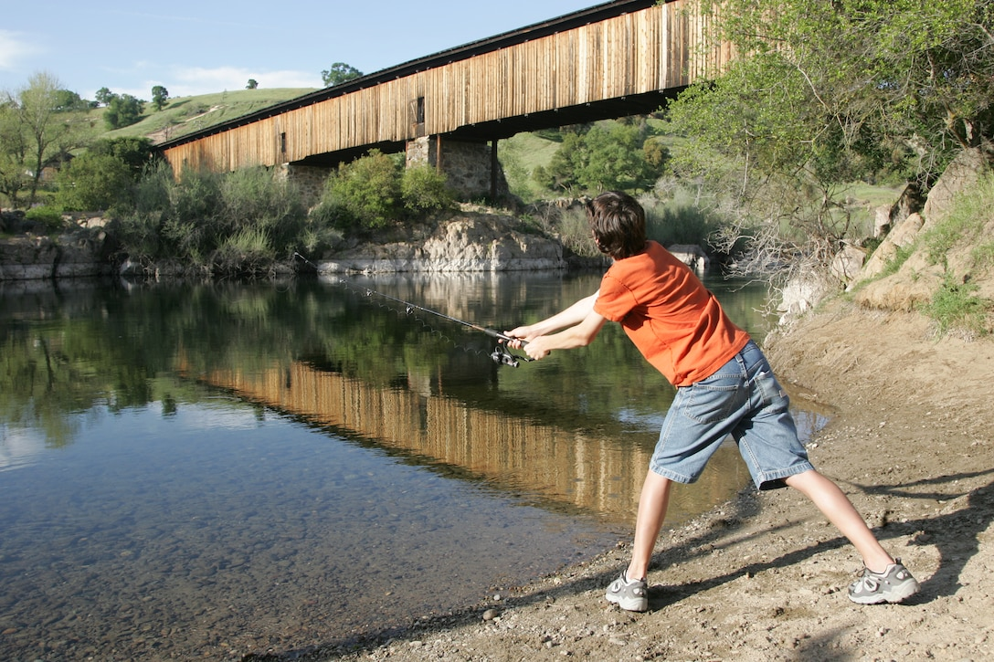 A young fisherman casts into the Stanislaus River, just below the scenic covered bridge.