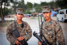 Lance Cpls. John L. Culilap (right), a field wireman with Combat Logistics Battalion 3, and Lance Cpl. Jed A. Delos-Reyes, a motor transportation operator with Headquarters Battalion, 3rd Marine Division, provide security at the camp at Crow Valley, during Balikatan 2012, April 17. Both Marines moved to California from the Philippines when they were young and have helped their unit by translating Tagalog for U.S. service members participating in the exercise.