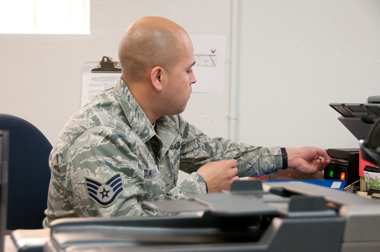 Staff Sgt. Jesus Cardona issues an ID card in the force support squadron Feb. 11. Starting in May the squadron will implement an appointment system to minimize wait times for customers. (U.S. Air Force photo/Tech. Sgt. Hollie Hansen)