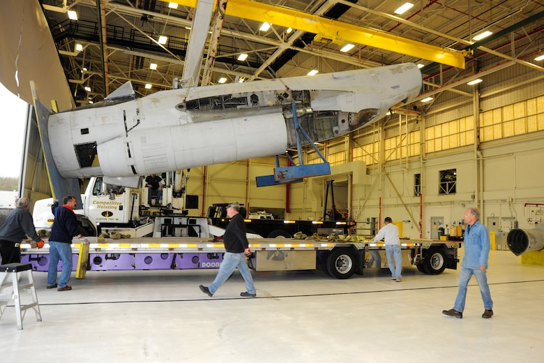 "Volunteers from the Selfridge Military Air Museum watch as a crane lifts the fuselage of an F-89 Scorpion off a flatbed truck into an aircraft hangar at Selfridge Air National Guard Base, Mich., April 16, 2012. Once finished, museum officials believe they will have the only restored F-89 ""C"" model on display in the country, possibly the world. (U.S. Air Force photo by SSgt. Rachel Barton)"