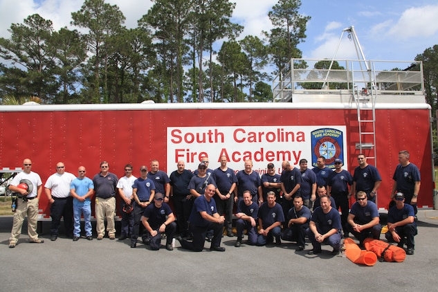 Air Station firefighters and instructors stand in front of one of the trailers used in the training exercise at the Structural Fire Department, April 18. The trailer contains a course with various obstacles and small spaces through which the firefighters had to maneuver.