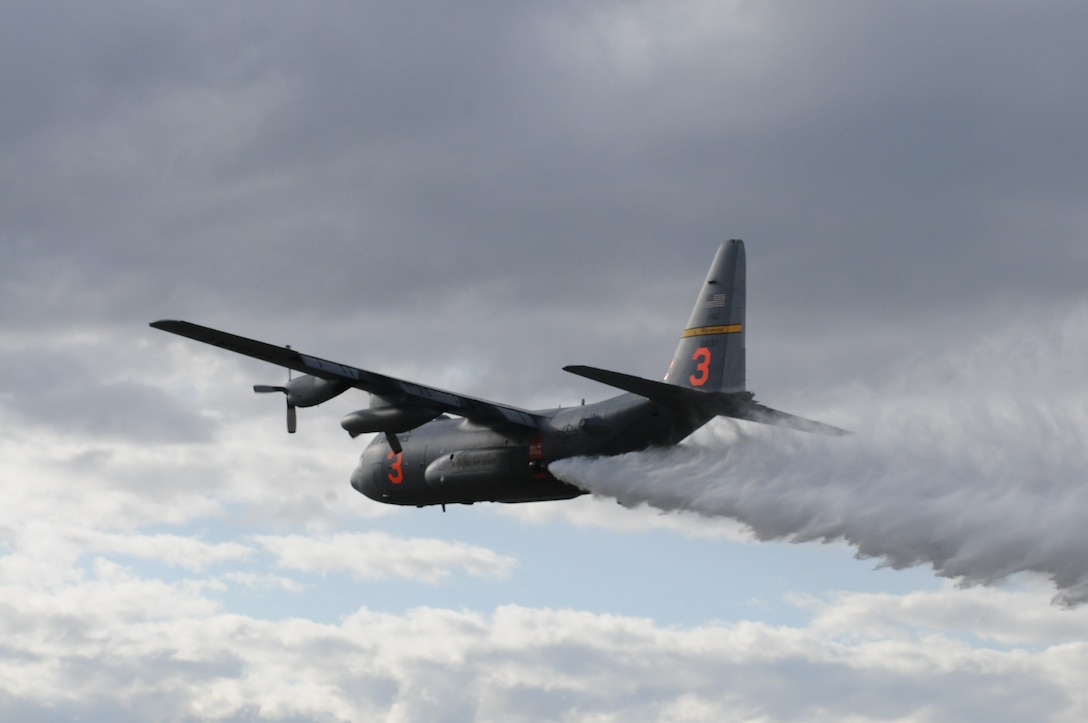 A C-130 assigned to the 153rd Airlift Wing, Wyoming Air National Guard, drops water during Modular Airborne Firefighting System (MAFFS) training April 16, 2012, over Camp Guernsey Joint Training Center, Wyo. Annual training is conducted to maintain currency and upgrade qualifications for pilots, aircrew and ground crews in preparation for the fire season. (Photo by Mr. Dewey Baars)